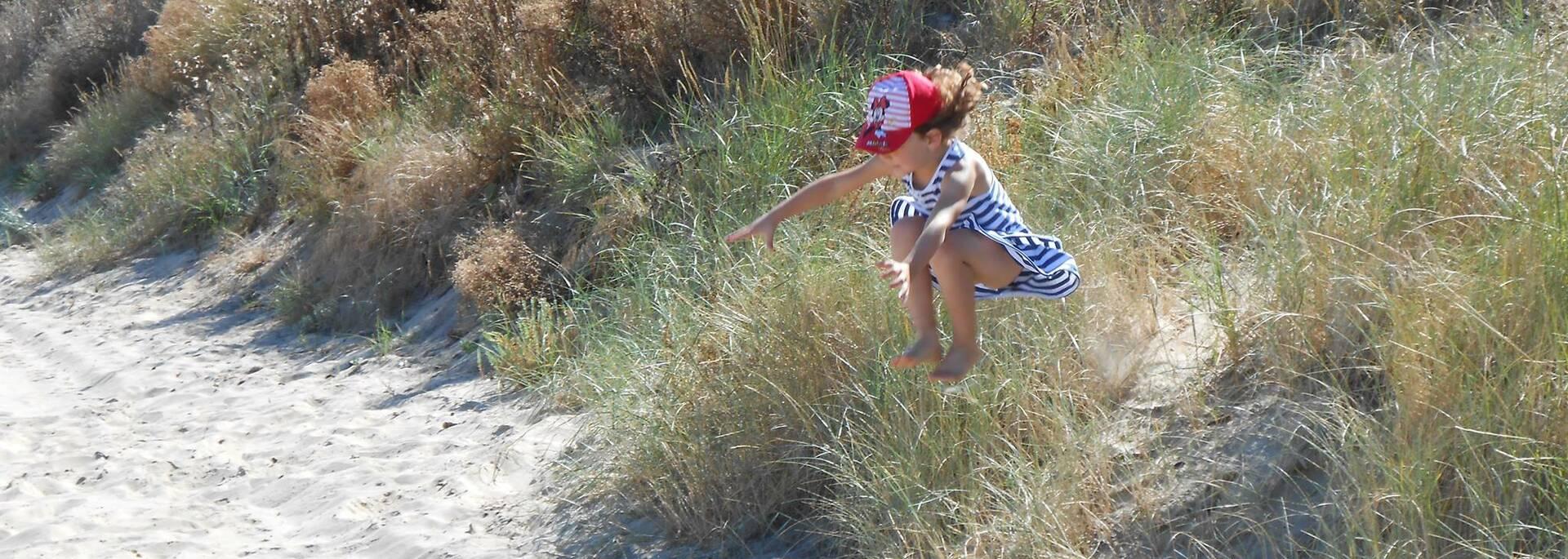 Enfant sautant dans les dunes de sable à Boyardville