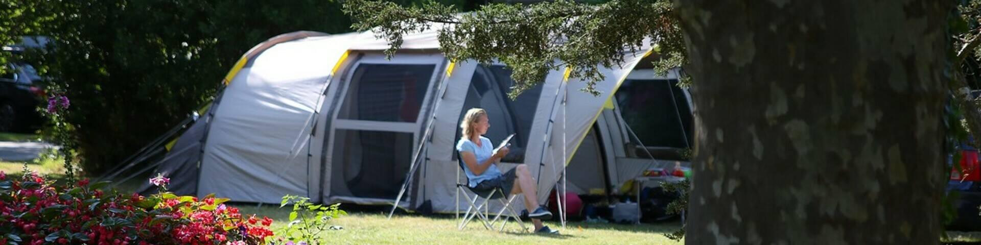 Lecture devant une toile de tente